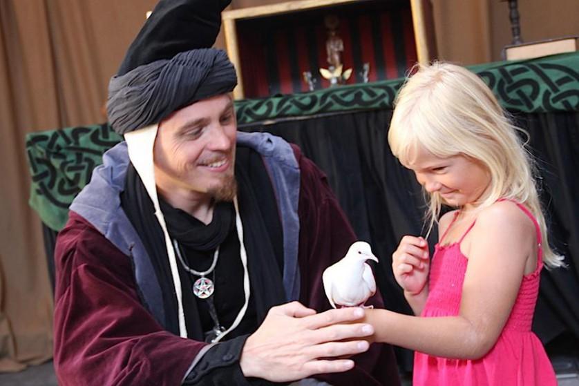 Gaston trollar med en duva tillsammans med en liten flicka